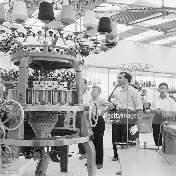 Spectators look at a new knitting machine at a trade fair at the Damascus International Fairgrounds in Syria