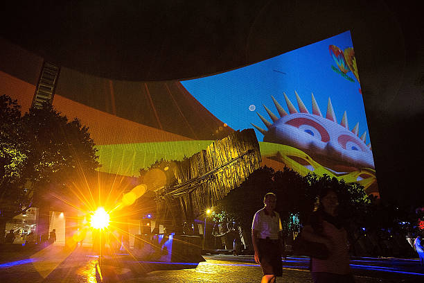 Spectators look at the 3D light show on the wall of Hong Kong Cultural  Centre and