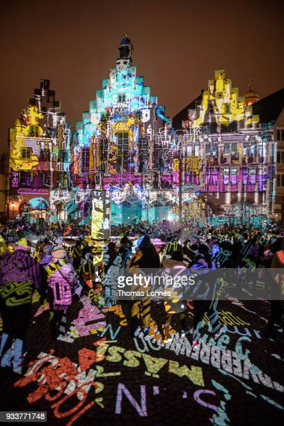 Spectators look at the 'light art/video mapping installation' of Philipp Geist at the 'Roemer' during the Luminale festival on March 18 2018 in...