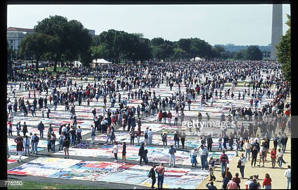 Spectators look at the National AIDS Memorial Quilt on the Mall October 12 1996 in Washington DC The AIDS Memorial Quilt is a tool for prevention...