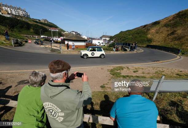 Spectators look on as a Mini Cooper is driven up the hill during the Saltburn Hill Climb event on September 08 2019 in SaltburnbytheSea England...