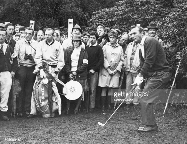 Spectators look on as Arnold Palmer of the United States plays an approach shot to the 3rd green during the Piccadilly World Match Play Championship...