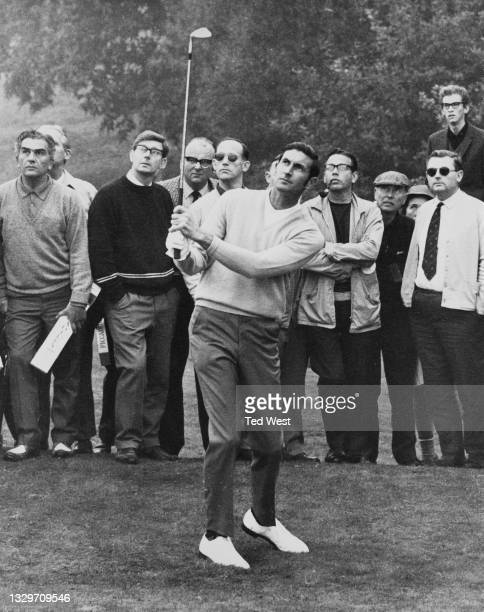 Spectators look on as Bob Charles of New Zealand plays an iron shot out of the rough on the 1st during the Piccadilly World Match Play Championship...