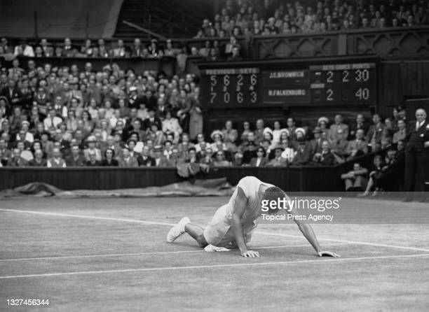 Spectators look on as Bob Falkenburg of the United States falls on his hands and knees during the final set of the Men's Singles Final match on...