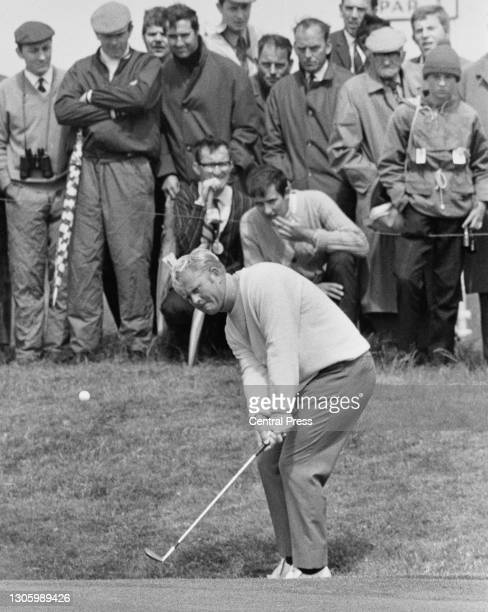 Spectators look on as Jack Nicklaus of the United States plays a chip shot onto the green during practice for the 98th Open Championship golf...