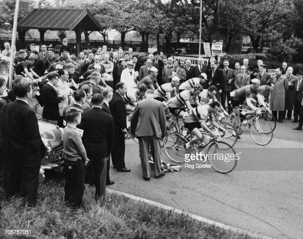Spectators look on as Minister of Agriculture John Hare drops the flag to start the cyclists off on the Round Britain Tour race on 26 May 1959 at...