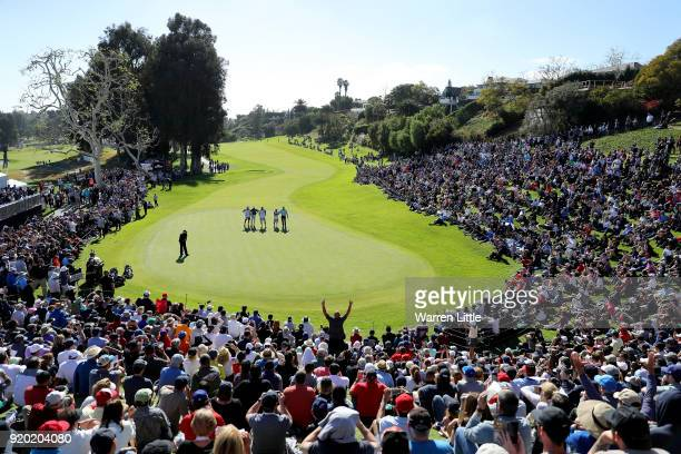 Spectators look on as Phil Mickelson putts on the 18th green during the final round of the Genesis Open at Riviera Country Club on February 18, 2018...