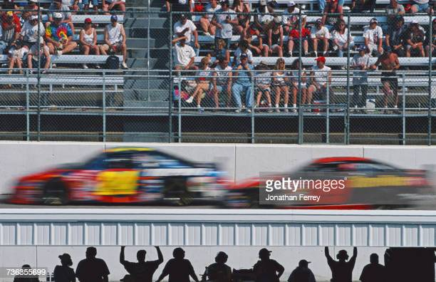 Spectators look on as Ricky Rudd driving the Texaco Halvoline Ford Taurus for Robert Yates Racing chases Jeff Gordon in the DuPont Hendricks...