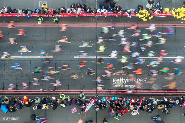 Spectators look on as runners cross the River Thames via Tower Bridge during the Virgin London Marathon 2016 on April 24 2016 in London England