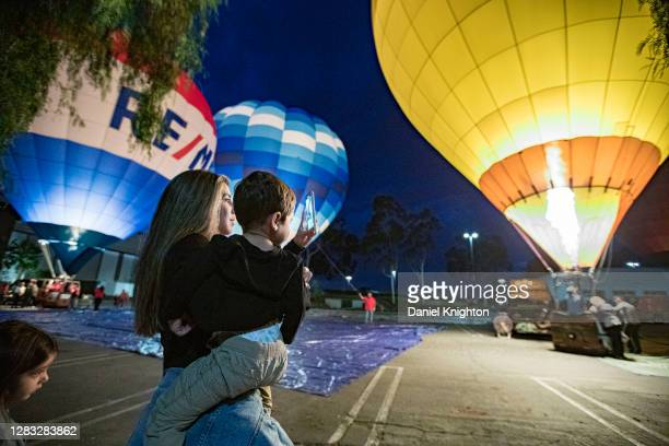 Spectators look on as tethered hot air balloons are illuminated by their burners at the Hot Air Halloween Balloon Glow on October 31, 2020 in...