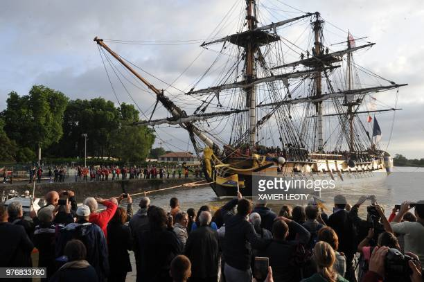 TOPSHOT Spectators look on as the replica of the French navy frigate L'Hermione which played a key role in the American Revolution sails the waters...