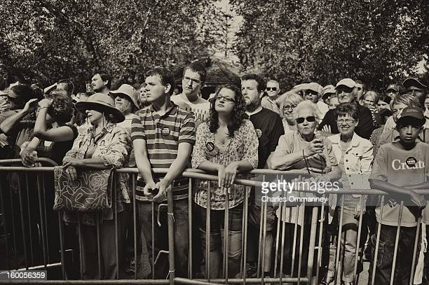 Spectators look on as US President Barack Obama delivers remarks during a campaign event at Herman Park in Boone Iowa on August 13 2012 Obama...