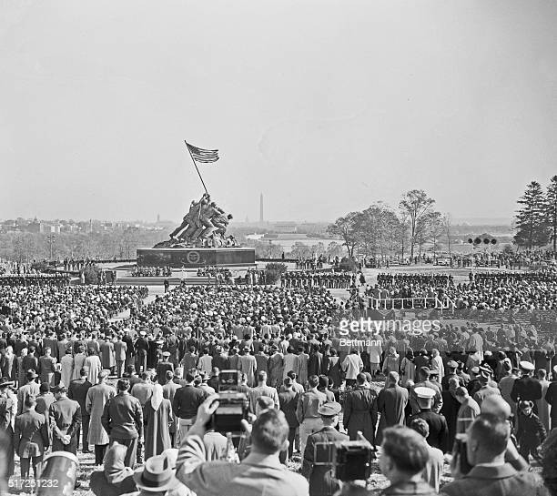 Spectators look on during the formal dedication of the US Marine Corps War Memorial near Arlington National Cemetery Depicting the flag raising on...