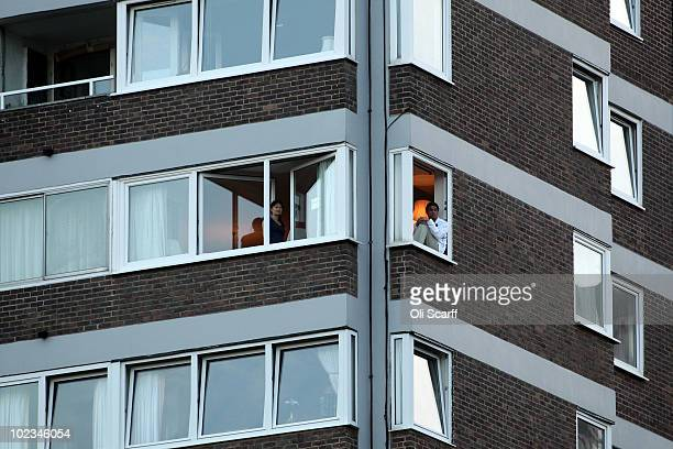 Spectators look on from a nearby apartment block as Nicolas Mahut and John Isner's match is stalled at 59 59 in the last set on Day Three of the...