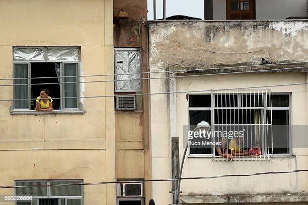 Spectators look on from nearby windows during the Men's Marathon on Day 16 of the Rio 2016 Olympic Games at Sambodromo on August 21 2016 in Rio de...
