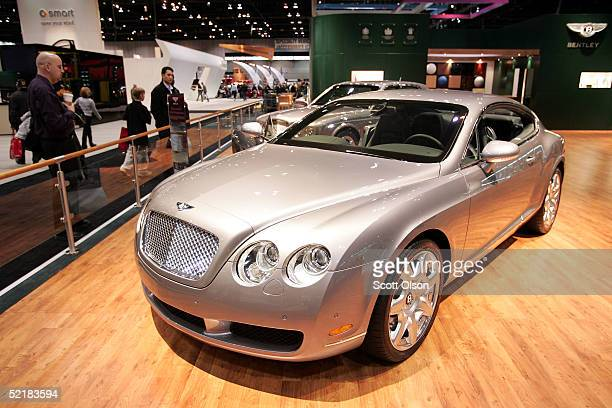 Spectators look over a Bentley Continental GT at the Chicago Auto Show on February 11 2005 in Chicago Illinois The luxury coupe does 060 milesperhour...