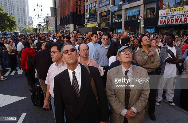 Spectators look up as the World Trade Center goes up in flames September 11 2001 in New York City after two airplanes slammed into the twin towers in...