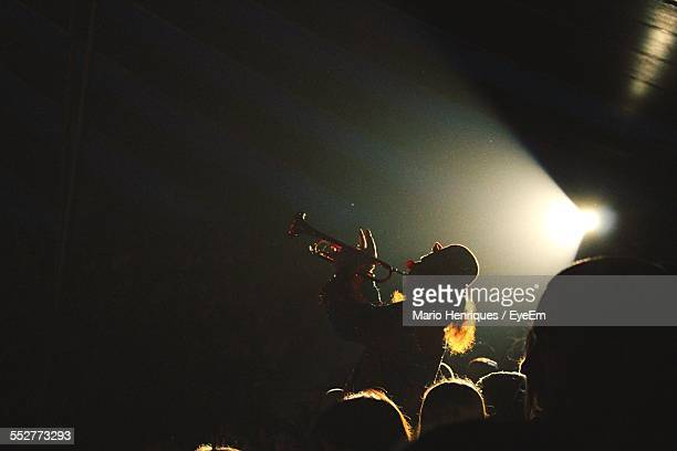 spectators looking at clown playing trumpet in circus - circus stock pictures, royalty-free photos & images
