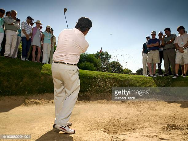 Spectators looking at male golfer in sand trap