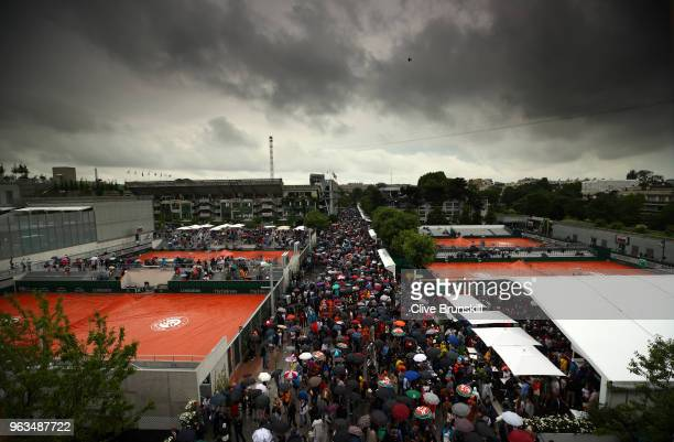Spectators make their way out of the ground during a rain delay on day three of the 2018 French Open at Roland Garros on May 29 2018 in Paris France