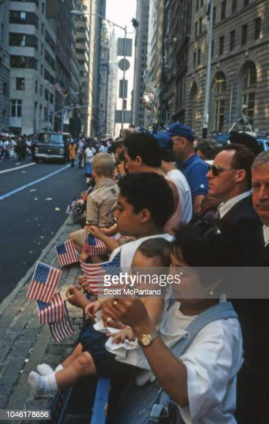 Spectators many with miniature American flags stand behind NYPD barricades on Broadway's Canyon of Heroes during a ticker tape parade for Desert...