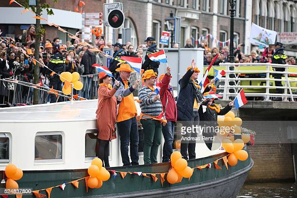 Spectators on a boat wave to the Dutch Royal family passing by them also on a boat during King's Day , the celebration of the birthday of the Dutch...