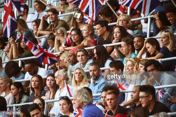 spectators on a stadium with british flags - crowd stock pictures, royalty-free photos & images