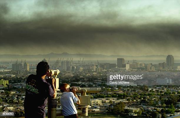 Spectators on Signal Hill watch as toxic smoke blows over downtown Long Beach CA April 23 from a fire at the Tosco oil refinery in Carson 15 miles...