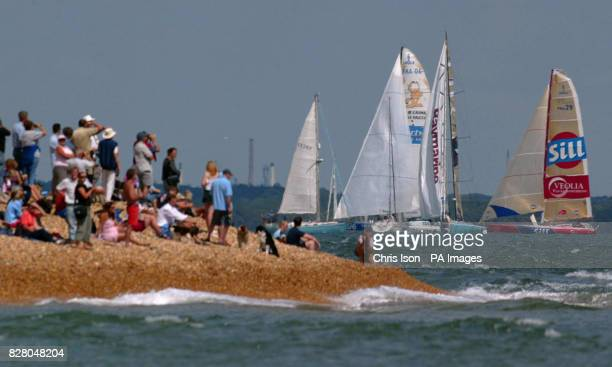 Spectators on the beach at Hurst Spit in Hampshire watch the Open 60 fleet start of the race