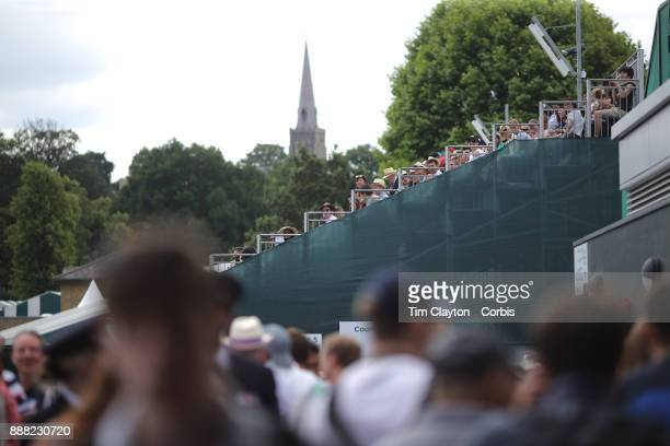 Spectators on the outside courts with Wimbledon village St Mary's church in the distance during the Wimbledon Lawn Tennis Championships at the All...