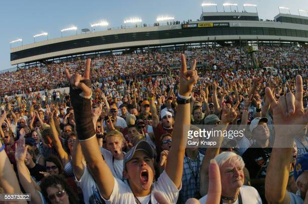 Spectators on the track and in the stands cheer as the recording group 'Nickelback' performs before the NASCAR Nextel Cup Series Chevy Rock Roll 400...