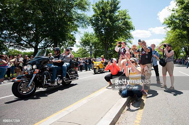 CONTENT] Spectators photograph SSgt Tim Chambers as he salutes riders coming down 23rd Street