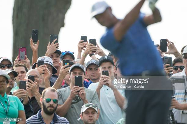 Spectators photograph Tiger Woods of the United States on their smart phones as he tees off on the thirteenth tee during round one of The Northern...