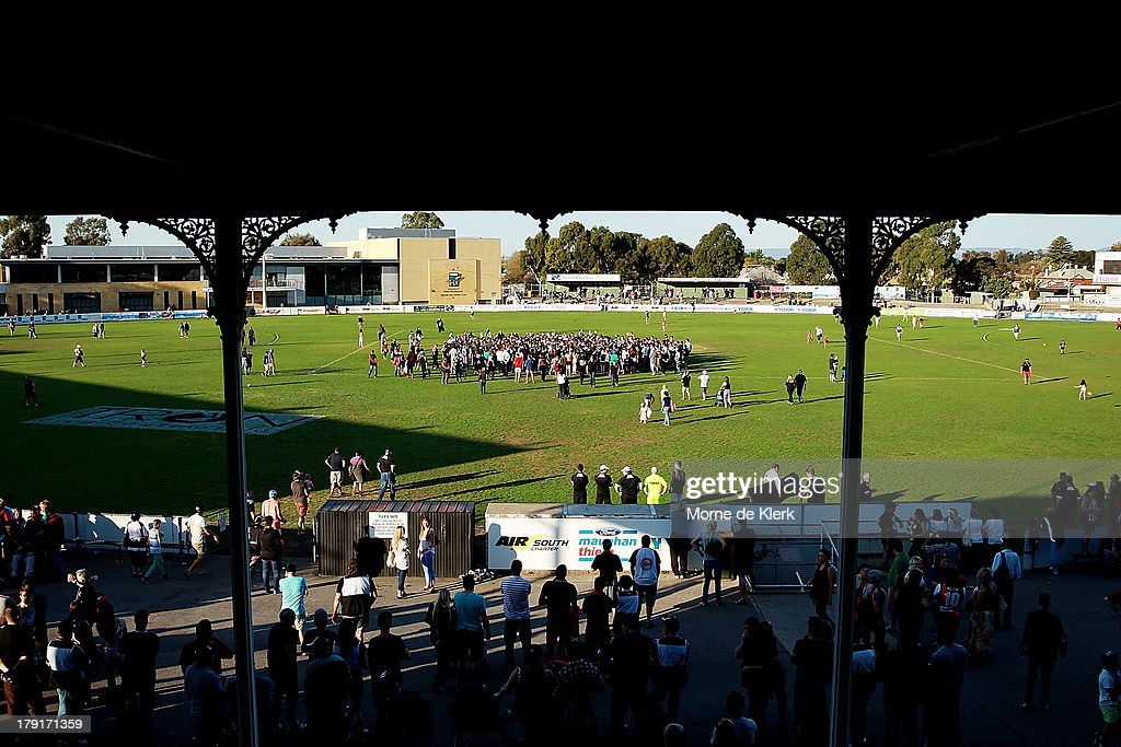 Spectators pour onto the field and swamp the players after the round 22 SANFL match between the Port Adelaide Magpies and the West Adelaide Bloods at Alberton Oval on September 1, 2013 in Adelaide, Australia.