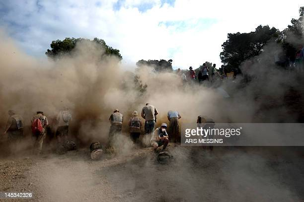Spectators protect themselves from the dust at the Agioi Theodoroi special stage of the WRC Acropolis rally in Loutraki on May 27 2012 AFP PHOTO /...