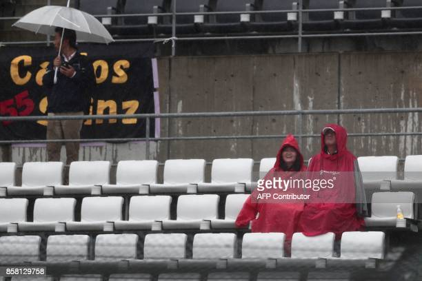Spectators protect themselves from the heavy rain as the start of second practice round of the Formula One Japanese Grand Prix is delayed at Suzuka...