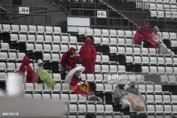 Spectators protect themselves from the heavy rain as the start of the second practice round of the Formula One Japanese Grand Prix is delayed at...