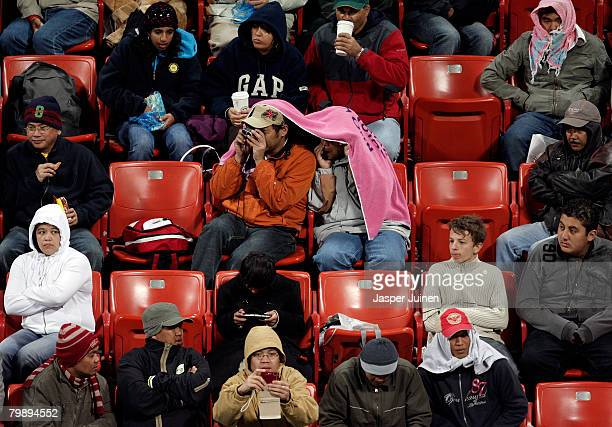 Spectators protect themselves some with a towel and some with hats from the cold and the heavy wind during day four of the WTA Qatar Total Open match...