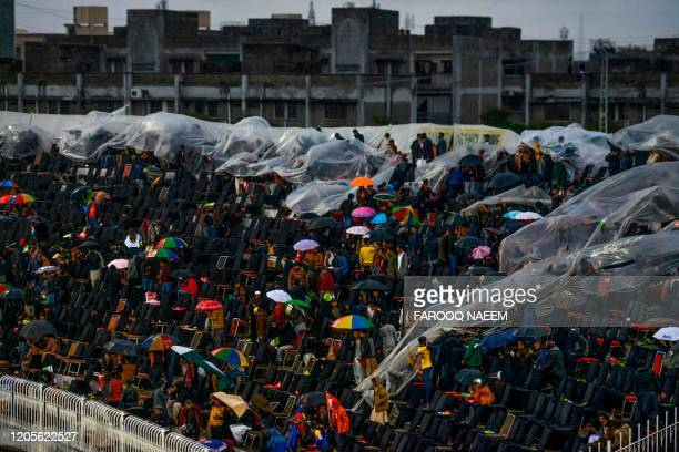Spectators protect themselves under umbrellas and plastic tarpaulin after the match has stopped due to rain during the Pakistan Super League T20...