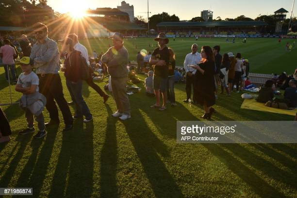 Spectators queue up for burgers as the sun sets over the North Sydney Oval during tea on the first day of the women's Ashes cricket Test between...