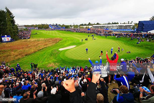 Spectators react as Rory McIlroy of Europe celebrates a hole winning putt on the 1st green during the Singles Matches of the 2014 Ryder Cup on the...