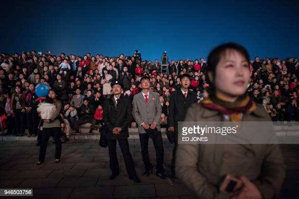TOPSHOT Spectators react during a fireworks display over the Taedong river during celebrations marking the anniversary of the birth of late North...
