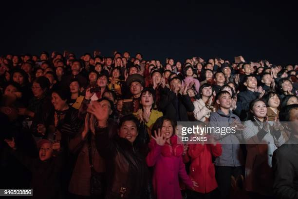 Spectators react during a fireworks display over the Taedong river during celebrations marking the anniversary of the birth of late North Korean...