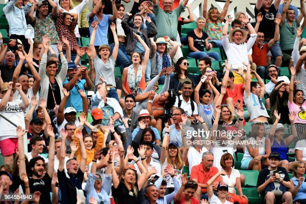 Spectators react during the women's singles second round match between Serena Williams of the US and Australia's Ashleigh Barty on day five of The...