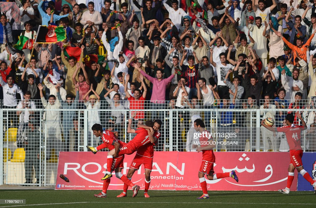 Spectators react in the stands as Afghan footballers celebrate after scoring a goal during their match against Pakistan at the Afghanistan Football Federation (AFF) stadium in Kabul on August 20, 2013. Afghanistan's football team sparked rowdy celebrations across the war-battered nation on August 20 after securing an convincing 3-0 win over arch-rivals Pakistan in the first international match in Kabul for ten years. AFP PHOTO/Massoud HOSSAINI