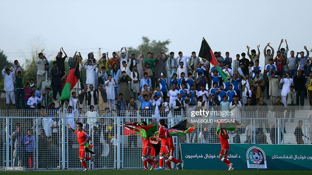 Spectators react in the stands as Afghan footballers celebrate their 3-0 win against Pakistan at the Afghanistan Football Federation (AFF) stadium in Kabul on August 20, 2013. Afghanistan's football team sparked rowdy celebrations across the war-battered nation on August 20 after securing an convincing 3-0 win over arch-rivals Pakistan in the first international match in Kabul for ten years. AFP PHOTO/Massoud HOSSAINI
