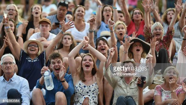 Spectators react on Henman Hill as Britain's Andy Murray wins against Italy's Fabio Fognini on the big screen at The All England Lawn Tennis Club in...