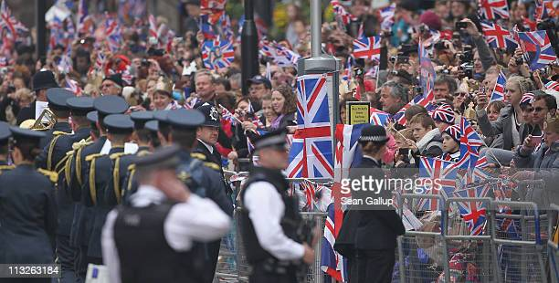 Spectators react to a passing marching band as they wait for the arrival of Prince William and Catherine Middleton along the procession route near...