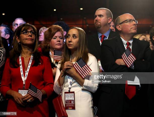 Spectators react to President Obama's projected reelection displayed on large televisions during Mitt Romney's campaign election night event at the...