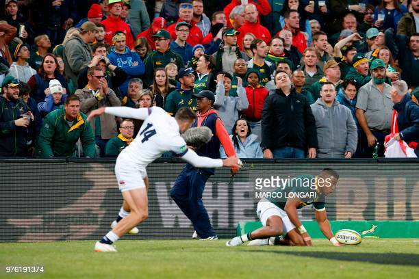 Spectators reacts as England winger Jonny May scores a try during the second test match South Africa vs England at the Free State Stadium in...